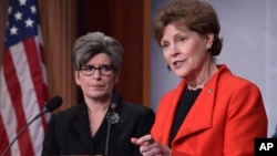 Sen. Jeanne Shaheen, D-N.H., right, standing with Sen. Joni Ernst, R-Iowa, announces in Washington, Feb. 7, 2018, a bipartisan resolution that would establish a special Senate committee to investigate the USOC and USA Gymnastics regarding how team doctor Larry Nassar was allowed to sexually abuse female gymnasts over decades.