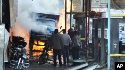 In this photo released by the Syrian official news agency SANA, Syrian citizens stand near a burning truck that was destroyed by two cars bombs in a suburb of Damascus, Syria, November 28, 2012.