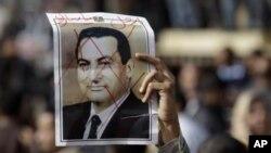 Демонстрант держит перчеркнутую фотографию президента Хосни Мубарака
