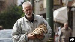 埃及一名男子拿着刚刚买到的面饼(2月6日)