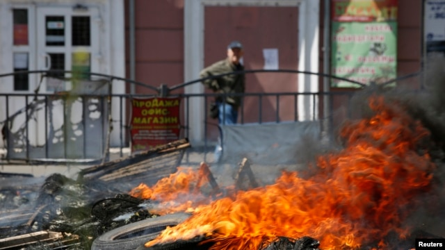 A man walks past a burning barricade near the city hall in Mariupol, eastern Ukraine May 10, 2014.