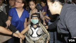 Mantan Presiden Filipina Gloria Macapagal Arroyo (tengah) meninggalkan bandara Manila, Filipina, setelah gagal pergi berobat ke luar negeri karena dihalangi petugas (15/11).