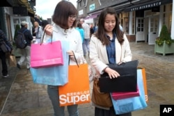 FILE - Shoppers carry designer label branded bags at a designer outlet center, in Bicester, England, Aug. 26, 2015. Chinese customers have become a powerful market force in the global trade in expensive clothes, jewelry, watches and handbags.