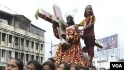 Para wanita penganut agama Katholik di Manila berjalan bertelanjang kaki menggusung replika Black Nazarene. Ribuan warga Filipina berpartisipasi dalam arakan tahunan patung kayu hitam Yesus dari Nazareth, Minggu (8/1). Patung ini dipercaya memiliki khasia