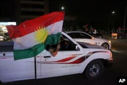 Iraqi Kurdish men celebrate as they wave Kurdish flags in the streets after the polls closed in the controversial Kurdish referendum on independence from Iraq, in Irbil, Iraq, Sept. 25, 2017.
