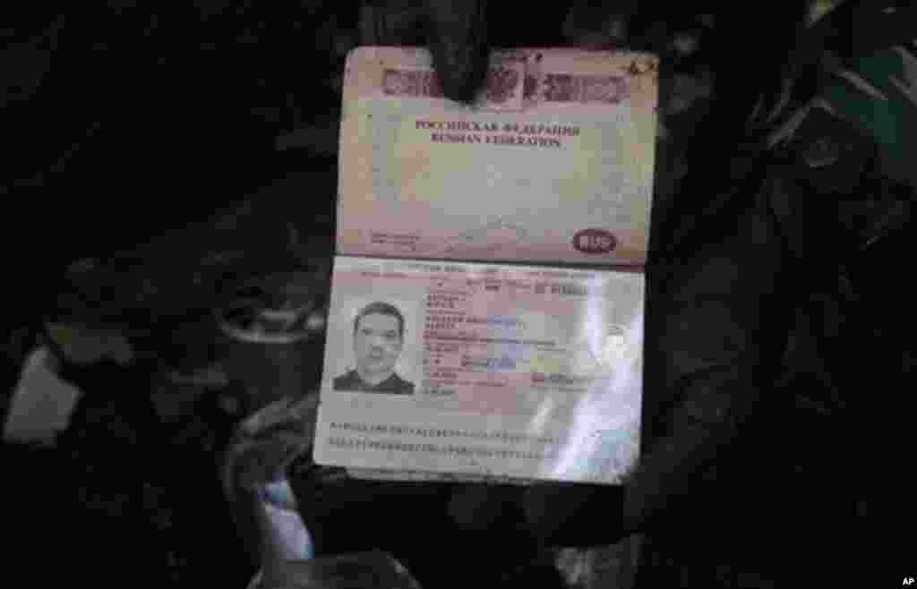 Passport of a flight engineer on the Sukhoi Superjet-100 is held by a rescue worker at Mount Salak in Bogor, Indonesia, Friday, May 11, 2012. Search teams who scaled a volcano's steep slopes found at least 12 bodies Friday near the wreckage of a Russian-m