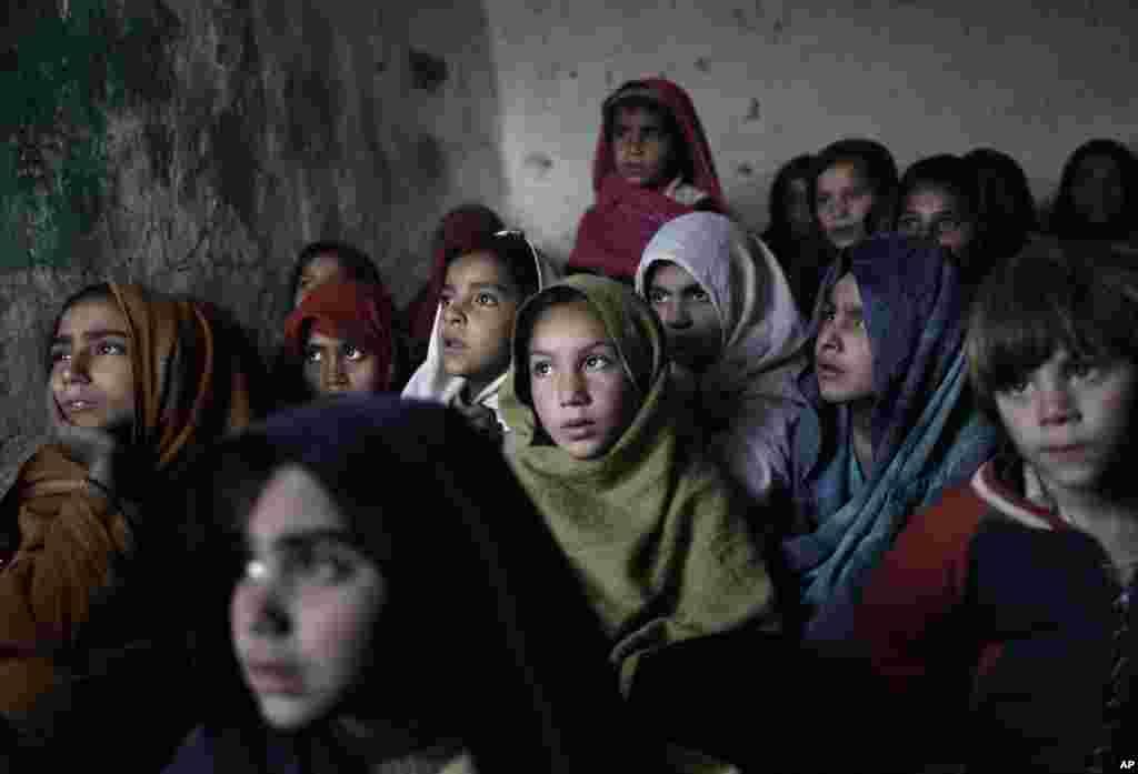 Murid-murid sekolah mendengarkan gurunya pada kunjungan petugas kesehatan ke sekolah mereka di pinggir kota Islamabad untuk memberikan vaksin polio (31/1). (AP/Muhammad Muheisen)