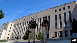 Petugas berjaga-jaga di luar Pengadilan Distrik Federal AS di Washington (28/6), tempat tersangka serangan Benghazi, Ahmed Abu Khattala, disidang. (AP/Jose Luis Magana)