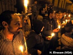 "Egyptian Copts seen lighting candles during a vigil in front of the ""Botrosia"" church, 35 were announced injured in Abbassya as they attended a vigil in Cairo, Dec. 11, 2016."