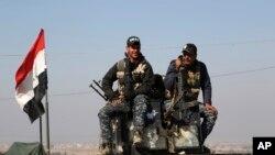 ຕຳຫຼວດຂອງອີຣັກ ສອງຄົນ ນັ່ງຢູ່ເທິງ ລົດຫຸ້ມເກາະ ຂອງພວກເຂົາເຈົ້າ ໃນຂະນະທີ່ ພວກຕຳຫຼວດລັດຖະບານກາງ ໄດ້ຖືກສົ່ງໄປປະຈຳການ ຫຼັງຈາກທີ່ໄດ້ຍຶດຄືນການຄວບຄຸມ ຂອງເມືອງ Abu Saif, ຢູ່ພາກຕາເວັນຕົກ ຂອງເມືອງ Mosul ຂອງອີຣັກ, ວັນທີ 22 ກຸມພາ 2017.