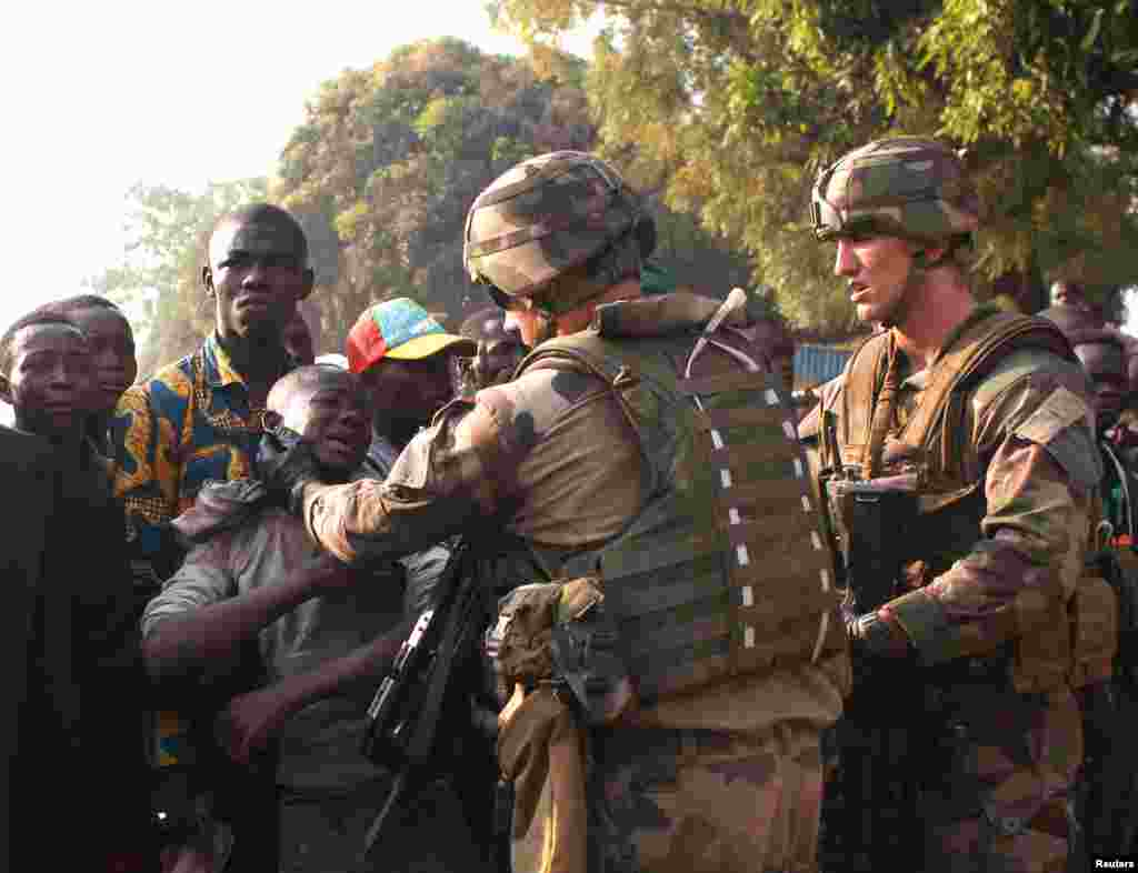 French military personnel try to control supporters who are asking them to disarm fighting gangs, near the airport in Bangui, Central African Republic. France appealed to European partners for assistance in quelling months of religious violence in its former colony.