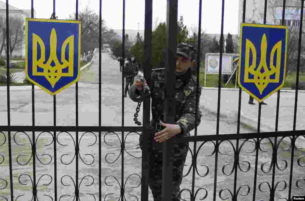 A Ukrainian soldier closes an entrance gate at the air force base in the Crimean town of Belbek, March 20, 2014.