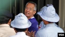 Veera Somkwamkid, satu-satunya warga Thailand yang masih ditahan, digiring dari ruang pengadilan oleh polisi Kamboja.