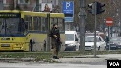 Seorang pria bersenjata yang belum diidentifikasi berdiri di tengah sebuah jalan di Sarajevo, dekat Kedutaan AS (28/10).