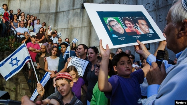 A boy holds a board with the likeness of three teenagers who had been kidnapped in Israel during a memorial service near the United Nations headquarters in New York, June 30, 2014.