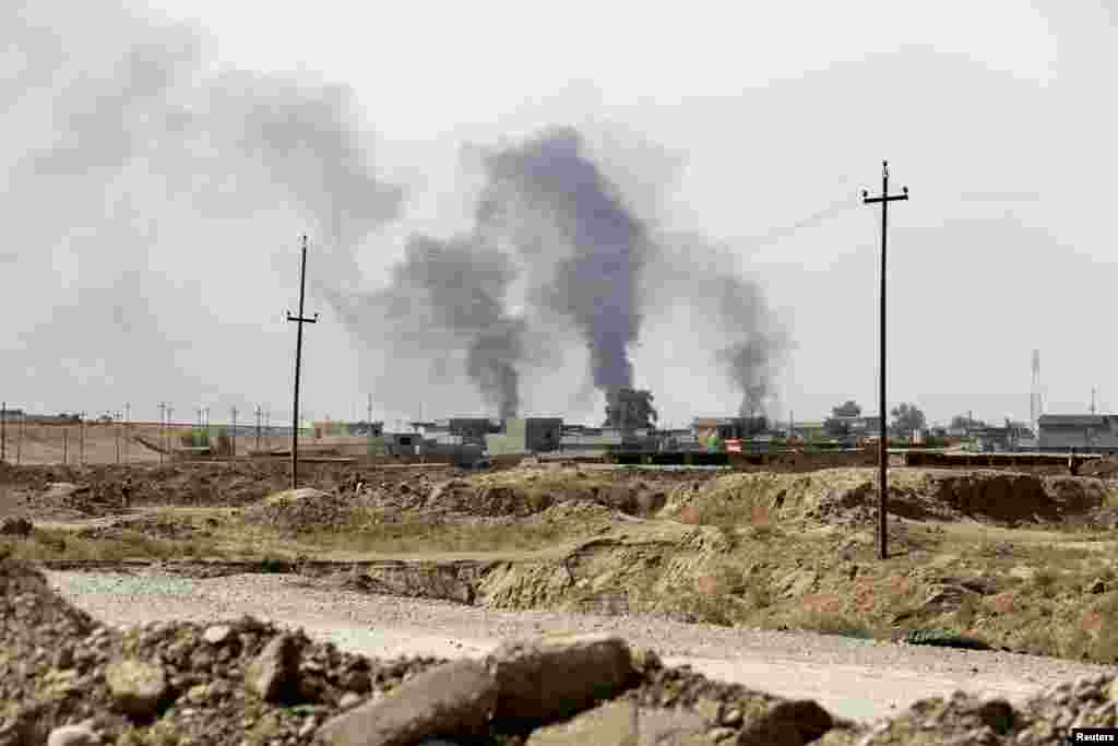Smoke rises from Sulaiman Bek after fighters of the Asaib Ahl al-Haq Shi'ite militia from the south of Iraq and Kurdish peshmerga forces took control of the town from Islamist State militants, in the northwest of Tikrit city, Sept. 1, 2014.