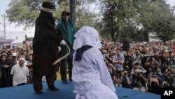 A Shariah law official whips a woman who is convicted of prostitution during a public caning outside a mosque in Banda Aceh, Indonesia, April 20, 2018. Indonesia's deeply conservative Aceh province on Friday caned several unmarried couples for showing affection in public and two women for prostitution.