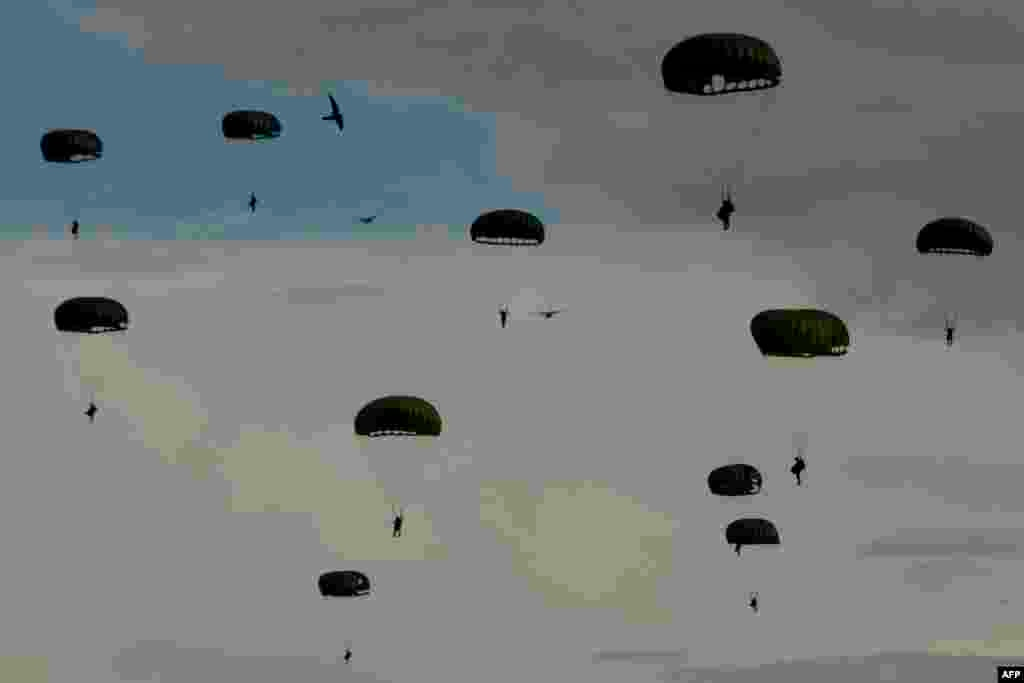 Indonesian paratroopers come down with their chutes during the Jalak Sakti military exercise held at the Sultan Iskandar Muda Air Force Base in Blang Bintang, Aceh province.