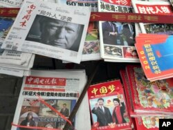 "FILE - A front page of a Chinese newspaper with a photo of U.S. President-elect Donald Trump and the headline ""Outsider counter attack"" is displayed at a newsstand in Beijing, China, Nov. 10, 2016."