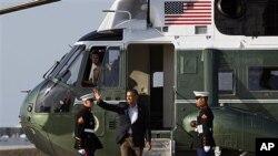 ປະທານາທິບໍດີບາຣັກ ໂອບາມາ ໂບກມືໃສ່ປະຊາຊົນ ຫລັງຈາກລົງຈາກເຮລີຄອບເຕີ້ Marine One ເພື່ອໄປຂຶ້ນເຮືອບິນປະຈໍາຕໍາແໜ່ງ Air Force One ທີ່ນະຄອນ Chicago ເພື່ອອອກເດີນທາງໄປຮ່ວມ ກອງປະຊຸມກຸ່ມ G-20 ທີ່ເມັກຊິໂກ, ວັນທີ 17 ມີຖຸນາ 2012.