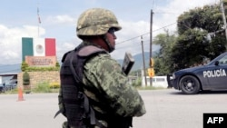 FILE - A Mexican soldier stands guard at a checkpoint in Guerrero State, Mexico, Sept. 29, 2014.