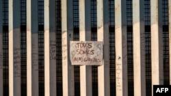 """En la foto de archivo se ve un letrero en la frontera entre Estados Unidos y México que dice en español """"todos somos migrantes"""", en Playas de Tijuana, noroeste de México."""