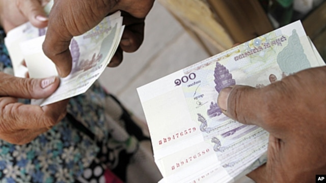 A man working at a money exchange (R) passes 100 Cambodian riel notes to a client  in central Phnom Penh, March 12, 2011 (file photo)