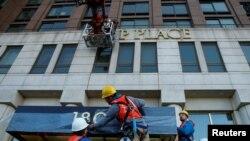 Fəhlələr Manhattanın Upper West Side məhəlləsində Trampın adını binanın üzərindən qoparırlar. Nyu York, ABŞ. 16 noyabr, 2016 REUTERS/Brendan McDermid