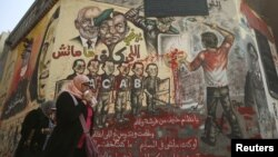 Egyptians walk past graffiti on a wall at Tahrir Square in Cairo, January 16, 2013.