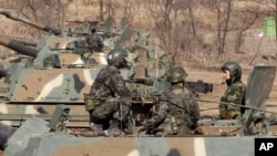 South Korean Army soldiers sit on their K-9 self-propelled artillery vehicle during an exercise against possible attacks by North Korea near the border village of Panmunjom in Paju, South Korea, March 11, 2013.