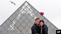 Sepasang turis AS mengambil swafoto di depan Piramida Louvre, Paris. (AP/Remy de la Mauviniere)