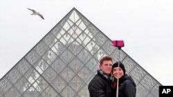 프랑스 루브르 박물관 앞에서 한 커플이 셀카봉으로 사진을 찍고 있다. (자료사진)
