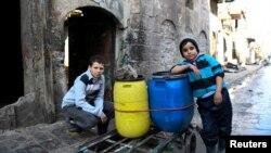 지난 1월 시리아 알레포 동부 지역에서 소년들이 물동이를 수레에 실어 집으로 나르고 있다.