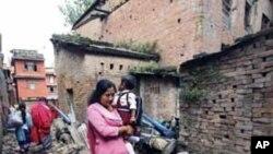 一名印度妇女走过被地震毁坏的房屋