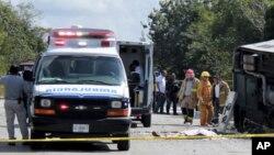 El cuerpo sin vida de un pasajero se encuentra al lado de un autobús volcado, mientras ambulancias, bomberos y policías, se encuentran en Mahahual, estado de Quintana Roo, México, el martes 19 de diciembre de 2017.