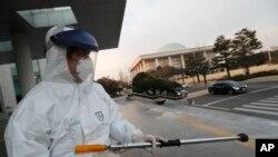 Nhân viên y tế mặc quần áo bảo hộ phun thuốc sát trùng tại toà nhà Quốc hội ở Seoul, Hàn Quốc, ngày 24/2/2020.