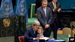 美国国务卿克里手臂中搂着他的孙女在联合国总部签署巴黎气候协议。(2016年4月22日)