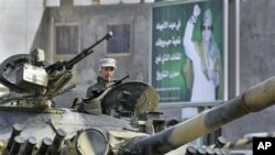 A Libyan army soldier loyal to Libyan leader Moammar Gadhafi, on poster in background, sits in a tank, in Qasr Banashir, southeast of the capital Tripoli, March 1, 2011