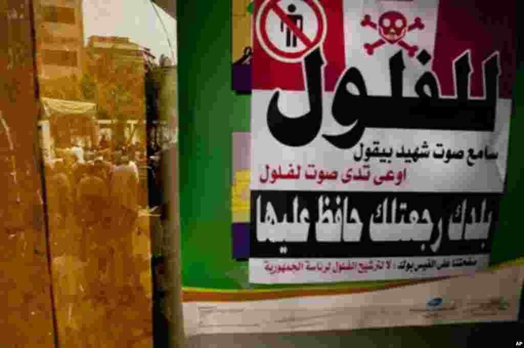 """Egyptian voters are reflected in a window where a sign hangs reading """"No to 'feloul' (remnants of the old regime). I hear the martyrs calling don't vote for a 'feloul,'"""" in Maadi, a southern suburb of Cario, Egypt on Wednesday, May 23, 2012. On Wednesday"""