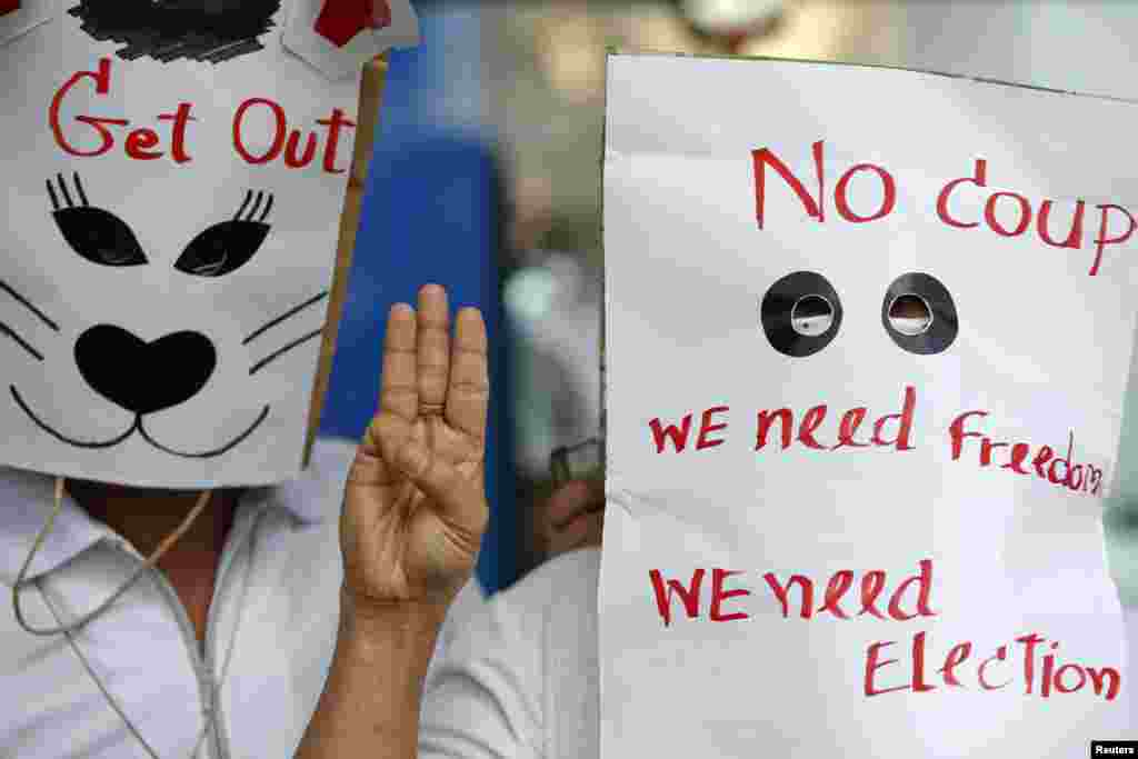 Anti-coup protesters wear paper bags with messages written on them as they flash a three-finger sign during a protest at a shopping mall in Bangkok, June 1, 2014.