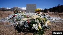 سنگ یادبود و گلهایی که در محل سقوط هواپیمای آلمانی در کوههای آلپ گذاشته شده است
