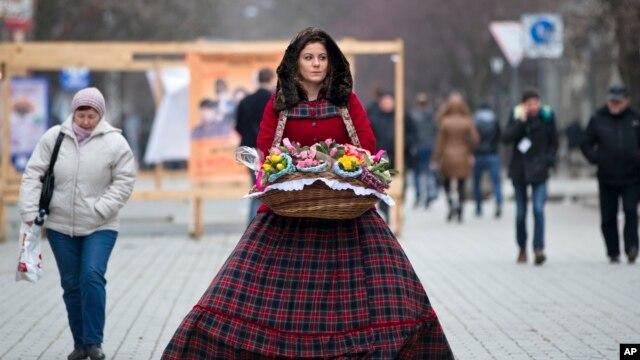 A flower vendor walks downtown Simferopol, Ukraine, March 9, 2014.