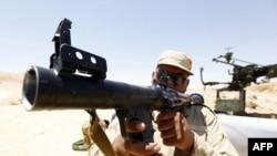 Một chiến binh phe nổi dậy đang kiểm tra khẩu súng tịch thu được của binh sĩ thuộc lực lượng của ông Gadhafi gần thị trấn Bir al-Ghanam