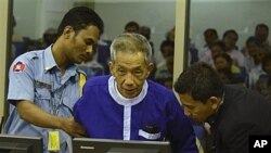 FILE - Kaing Guek Eav, alias Duch, who ran a prison where up to 16,000 people were tortured before being killed, comes before the Khmer Rouge war crimes tribunal in Phnom Penh, Cambodia, March 19, 2012.