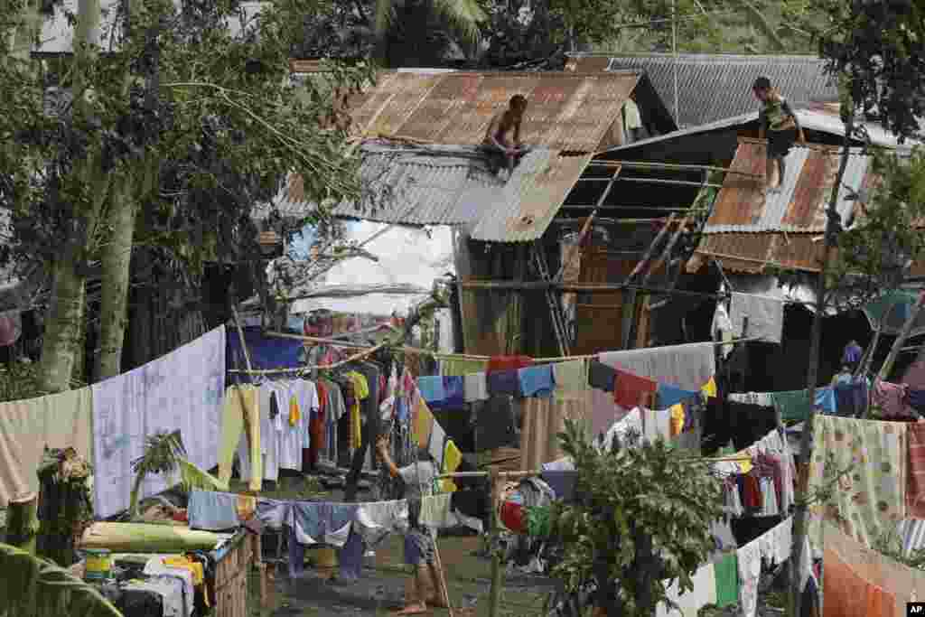 A family goes on their daily business Thursday, July 17, 2014, a day after Typhoon Rammasun hit Batangas city, Philippines.