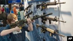 Un jovencito apunta con un fusil de asalto durante la convención anual de la NRA el fin de semana en Houston.