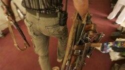 تصویر یک پلیس افغان و اسلحه هایی که از یک از شرکت های خصوصی تامین امنیت جمع آوری شده