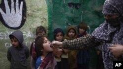 Seorang anak sekolah Pakistan tengah menerima vaksinasi polio dari petugas di pinggiran kota Islamabad, Pakistan (Foto: dok). Seorang polisi Pakistan ditembak mati saat melindungi tim vaksinasi polio di wilayah Waziristan, Selasa (26/2).