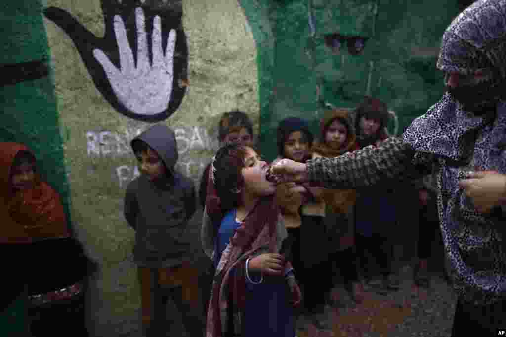 Murid sekolah Pakistan, yang harus meninggalkan rumah di wilayah timur laut bersama keluarganya konflik antara kelompok militan dan tentara pemerintah, mendapat vaksin polio dari petugas kesehatan di pinggir kota Islamabad (31/1). (AP/Muhammad Muheisen)