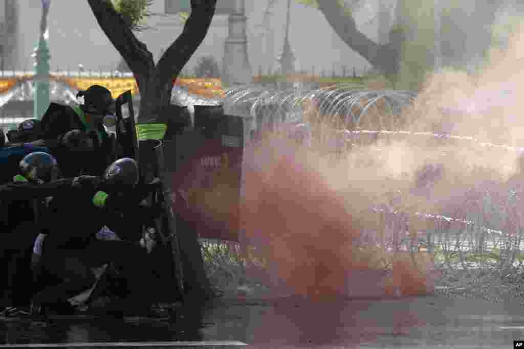 Riot police launch tear gas to protesters marching to Government House in Bangkok, Thailand.